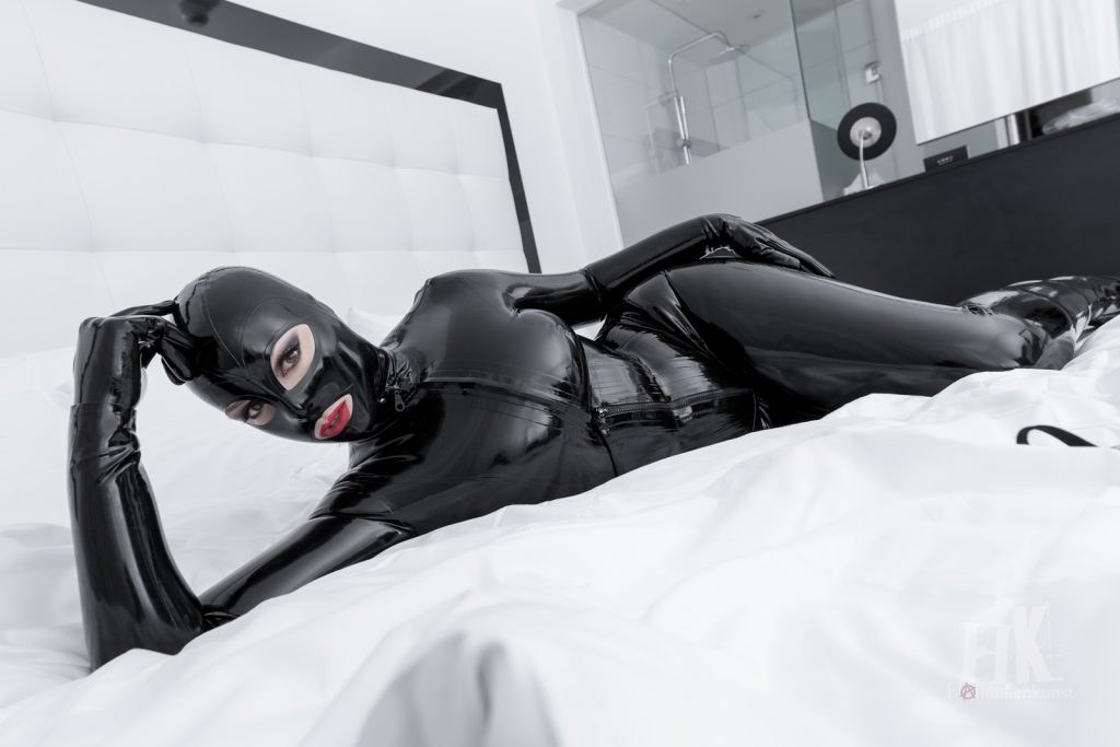 Latex-Göttin Miss Leonie in Vollgummierung im Hotelbett